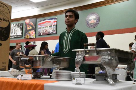 Dipto Mukherjee, '19, stands ready to serve attendees at the Indian food table. Dishes served included potato curry and mishti pulao.