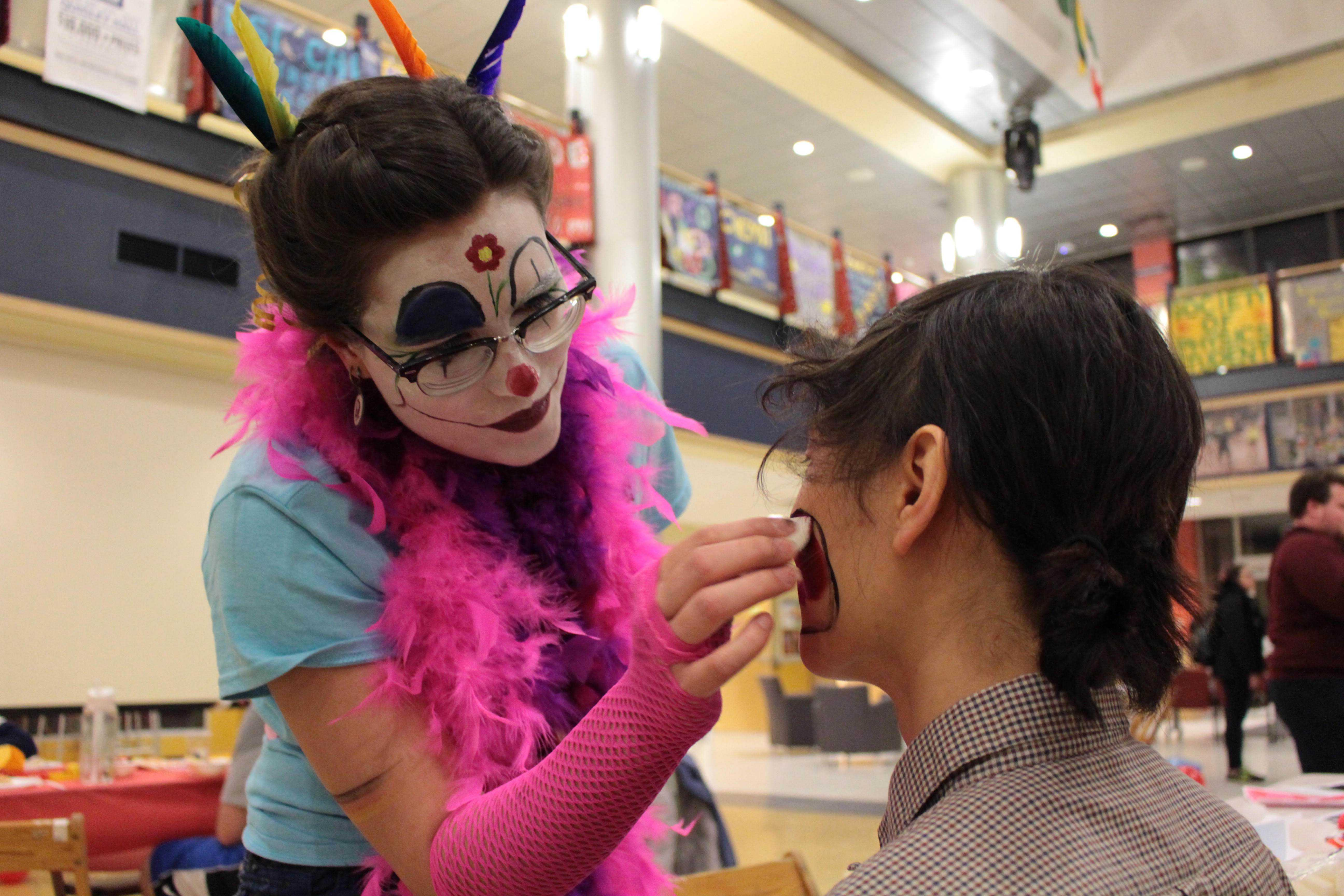Jasmin Wagner, a German teaching assistant paints the faces of people who came to the Carnival of Culture on Sunday, Feb. 26, 2017.