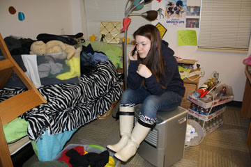 Sarah Bottini, '13, sits atop a dehumidifier in her flooded dorm room