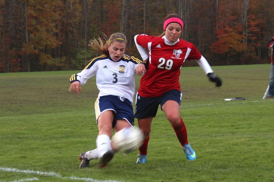 Jessie Thiessen, 2017, battles for the ball against a Hiram player during the NCAC match at Robertson Athletic Complex on October 23, 2013.  Later in the second half, Thiessen scored the Gator's second goal, bringing them closer to their fifth straight shutout.  Katie McMekin/THE CAMPUS