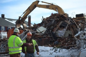 ran Janaszek (left)  from Kebort Construction talks with a coworker as rubble from the demolished apartment complex is moved to a dumpster on Jan. 30, 2014. The blaze left at least nine families without a home. The demolition began at approximately 10 a.m. and ended at 2 p.m.  Spectators gathered throughout the process, many taking photos and videos. CAITIE McMEKIN/THE CAMPUS