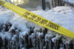 After the fire, caution tape was still posted around the property of  the aparment complex on Jan. 30, 2014.  Surrounding trees and pavement were  covered in ice from the water used to fight the fire. CAITIE McMEKIN/THE CAMPUS