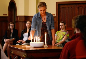 AMASA SMITH/THE CAMPUS Kelsey Sadlek, '14, lights a candle as Morgan Mechlenburgh, '15, Maddy Yemc, '17, and Alexandrea Rice, '17, look on during a prayer service in Ford Chapel on April 10, 2014. The service was held by the college for the victims of the Franklin Regional Senior High School stabbing earlier this week. Lead by College Chaplain Jane Ellen Nickell, participants prayed for victims and families affected.