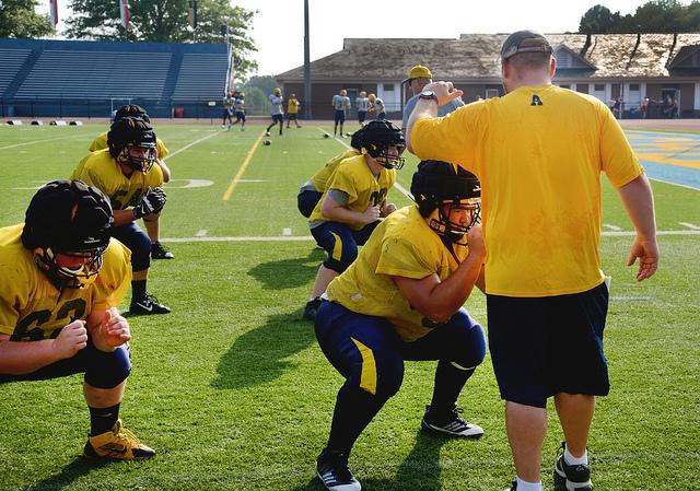 AMASA SMITH/THE CAMPUS Coach Ryan Jones helps Tyler Seibert, '16, during football practice at Robertson Field on Tuesday Aug. 26, 2014..