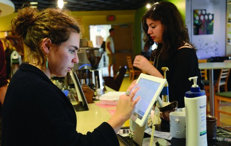 Katie Stanger, '16, waits as Maggie Dugan, '18, rings up her order in Grounds for Change.  Matthew Deutsch, '18, not pictured, helps Dugan prepare Stanger's coffee. Dugan and Deutsch are new student workers, volunteering their free time to run the coffee shop.
