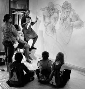 PHOTO BY RACHEL WANG/THE CAMPUS This year's theme focused on loss.Artist Steve Prince, back left, explain his drawing of to students in Allegheny College Art Gallery, during 8 Hour Projects on Saturday Aug. 30, 2014.