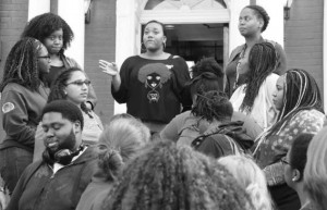 "MEGHAN HAYMAN/THE CAMPUS  Nia Burnett, '17, vice president of ABC, addresses the participants of the ""Hands Up, Don't Shoot"" photo after Imani Prince, '16, president of ABC, said she became too emotional to continue speaking"