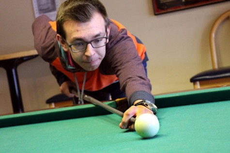 Ryan Tipker, '18, aims the cue during a daytime visit to the game room. Pool is one of the most popular games amongst students and faculty alike.