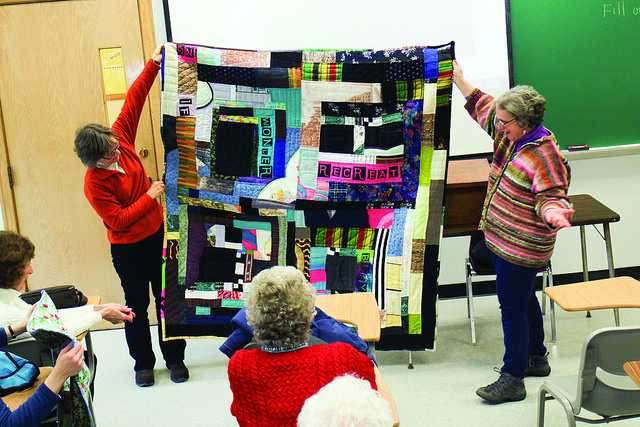Professor+Elizabeth+Ozorak+and+Louise+Silk+hold+one+of+Silk%E2%80%99s+quilts+after+her+presentation+on+Wednesday+Feb.+4.+%0A