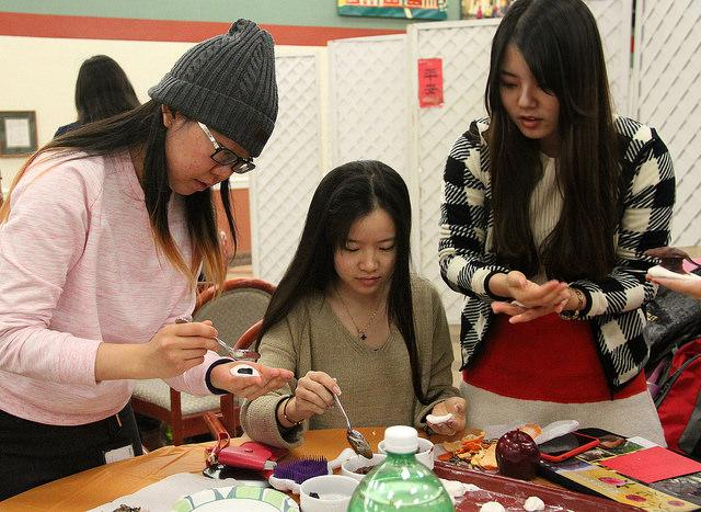 Shuyi Tang, '17, Wenjie Lin, '17, and Xiaoyu Zhu, '18, make Chinese rice balls filled with sesame, orange skin or red bean flavoring. The balls were boiled and then served with sugar while other performances continued in the Schultz Banquet Hall on Feb. 19.