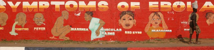A man walks by a mural that illustrates the symptoms of Ebola on the side of SKD Boulevard in Monrovia on Dec. 30, 2014.