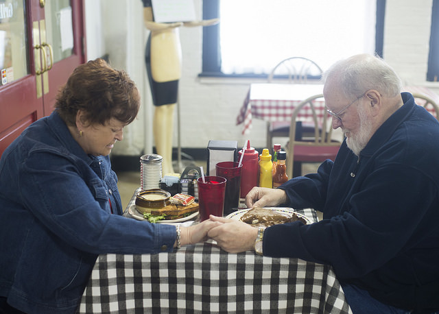 Peggy and John Hamilton pray before eating lunch at the Market House Grille. They've been eating at the restaurant for the nearly 50 years they've been married. Photo by Julia Moss.