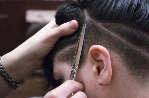 Crystal Ferry strategically cuts lines on Sydney Killburn's newly shaved head.