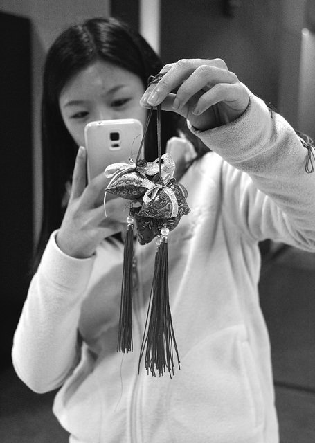 Lynn Lim, '15, president of A5, takes a picture of sachets made by students who participated the Dragon Boat Festival on Thursday, April 16.