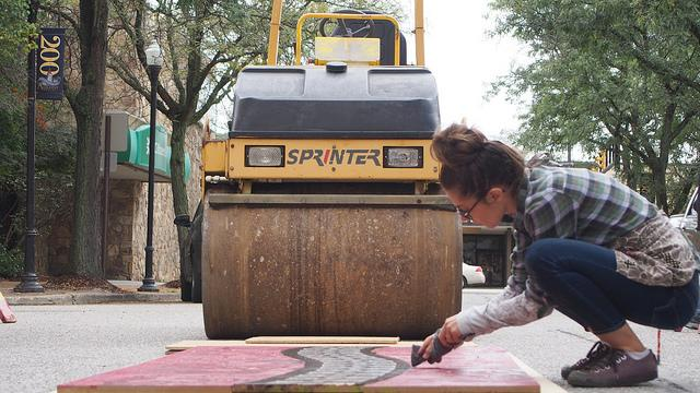 Amber Mosbacher, a resident of Meadville, touches up the ink on part of the wooden zipper before it is pressed by a steamroller.