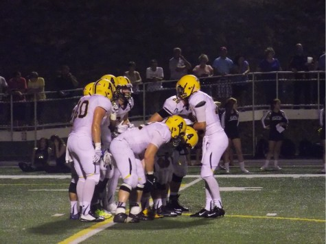 The Gator football team prepares for a new play during the game against Thiel College.