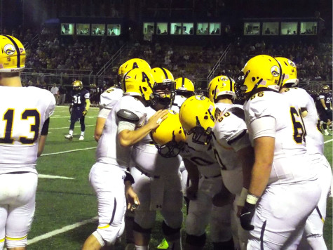 The Gator football team huddles during the game at Thiel College.