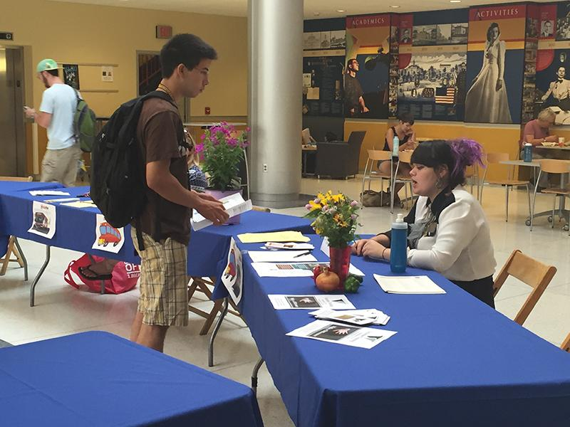 Spencer Subega, '18, talks with Heather Fish at the Davies Community Service Leaders table at the job fair.