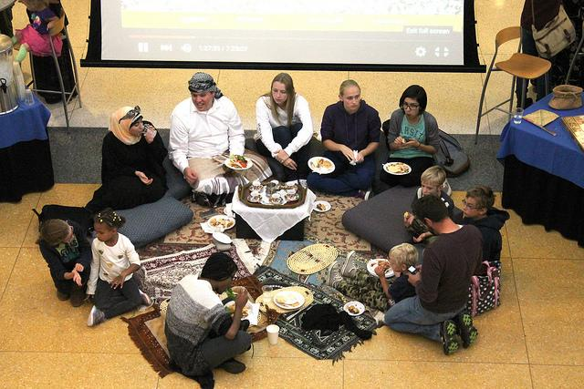 Students and Meadville community members gather around a tea table and enjoy authentic Middle Eastern food.
