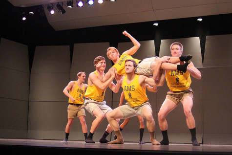 The Allegheny men's swimming and diving team flex their muscles on stage as they squat one of their teammates.