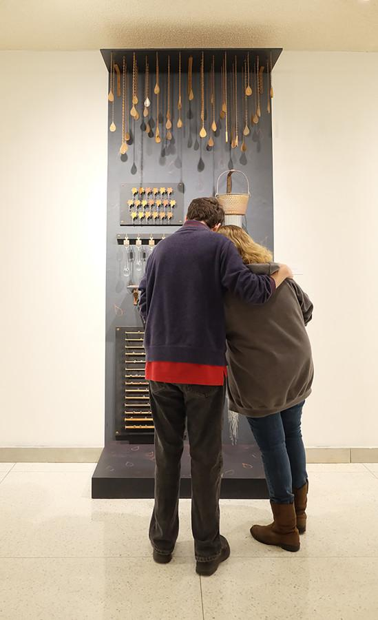 "Kevin Caler,  '16, and Gabriella Belt, '17, observe Jennifer Hecker's ""Oh, the Water"" mixed media installation. The piece is made with flameworked glass elements, found objects, steel, plywood, paint and red iron oxide."