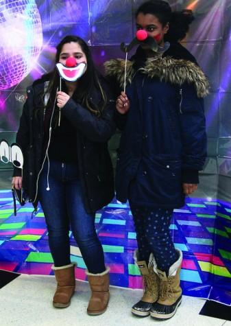 Danushka Cornejo, '19, and Vicquaja Mangal, '19, use props in the photobooth set up at Karneval in the campus center on Thursday, Feb. 18, 2016.