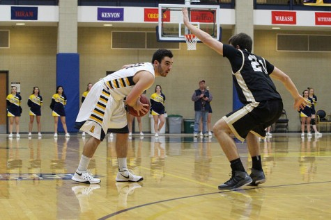 Billy Urso, '19, looks for a teammate to pass to during the first half of the game aginst the College of Wooster on Wednesday, Feb. 17, 2016. Urso scored a career high of 20 points against the Fighting Scots.