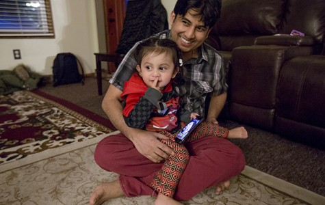 Tika Timsina, 32, holds his son, Adarsh Timsina, inside their home in Erie, Pennsylvania.