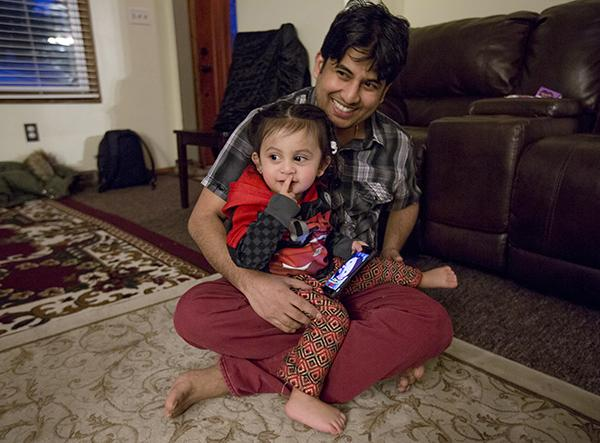 Tika Timsina, 32, holds his son, Adarsh Timsina, inside their home in Erie, Pennsylvania.