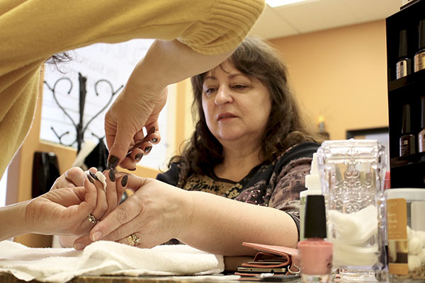 Galina Sadchikov, a refugee from Volgograd, Russia, gets her nails cleaned by salon owner, Tamara Kolesnichenko, on March 4, 2016. Sadchikov was a first-time customer.