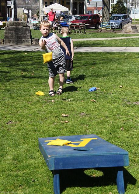 Landon Plyler tosses a bean bag in a game of Corn Hole, an activity ran by the Allegheny Football table in Diamond Park.