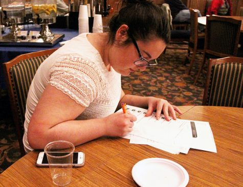 Sydney Fernandez, '17, participates in the panel discussion by writing her questions for the panelists on notecards at the table.
