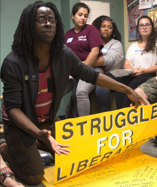 Darnell+Epps%2C+associate+director+of+the+Inclusion%2C+Diversity%2C+Equity%2C+Access+and+Social+Justice+Center%2C+displays+a+poster%2C+titled+%E2%80%9CStruggle+for+Liberation%2C%E2%80%9D+to+hang+in+the+Henderson+Campus+Center+during+a+meeting+on+Wednesday%2C+Sept.+7%2C+2016.+