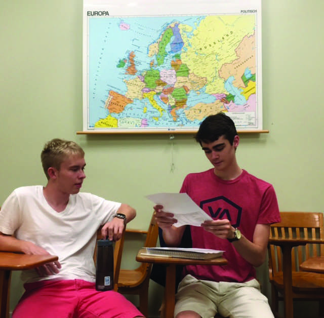Ben Devlin, '19, and Eric Pingel, '18, compare notes in Thomas Lang's creative writing class.