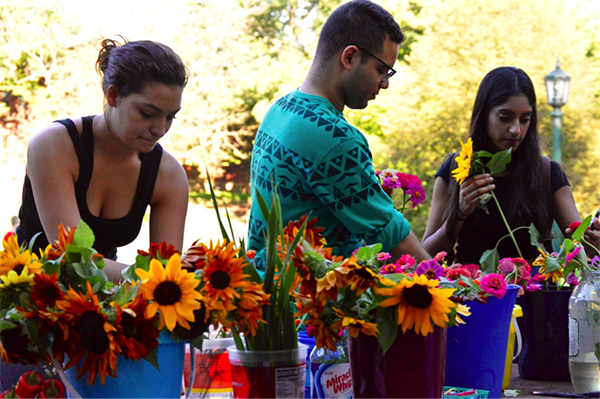 Meadville residents, Britani Ditch, Hilario Segarra and Sambrita Mally arrange flowers at the market on Brooks lawn before the DeHart Local Foods Dinner hosted in Schultz Banquet Hall on Wednesday, Sept. 21, 2016, at 6:30 p.m. Local farms provided fruits, vegetables and other foods that were served at the dinner.