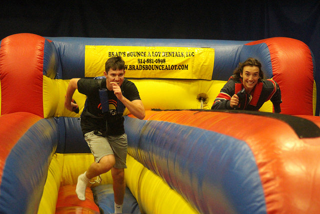 Vincent Carone, '20, and Francis Faiello, '20, race against each other in the Bungee Run Challenge. The object of the race is to place a baton as far down the two-laned course while running against the pull of the bungee cord they are harnessed into.