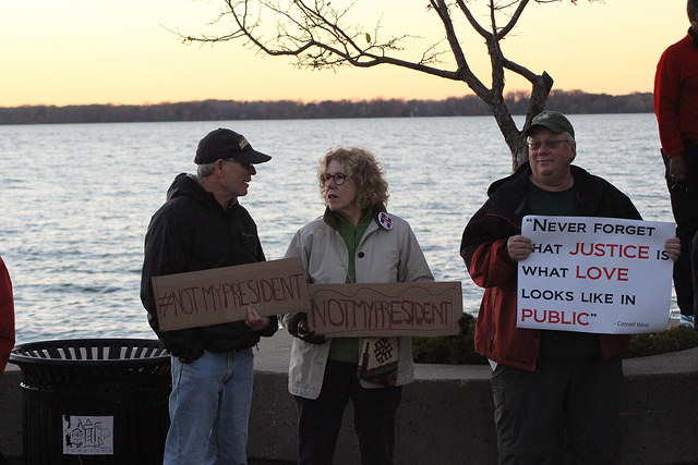 Erie residents John Morton, Georgana Ely and Tim Reim protest the election of Donald Trump near Bicentennial Tower in Erie, Pennsylvania, on Sunday, Nov. 13, 2016.