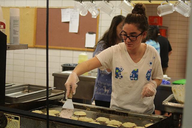 Shoshana Robbins, '19, makes latkes, a traditional Jewish dish, for Hillel's annual Hanukkah dinner.