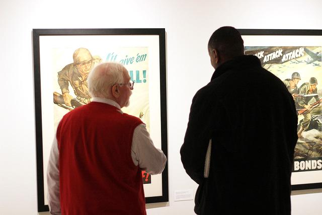 Professor of Art History Richard Schindler and Assistant Professor of Art Steve Prince discuss one of the pieces on display in the Doane Hall of Art in the Bowman-Penelec-Megahan Galleries on Tuesday, Jan. 24, 2017. The exhibition includes propoganda posters from World War I and II and Puerto Rico, as well as photographs from World War II.