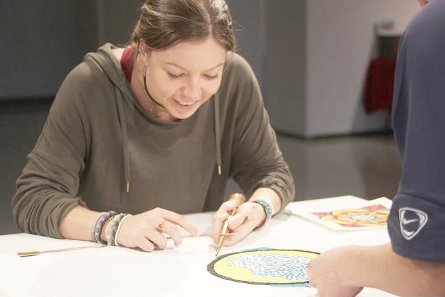 Nadiya Wahl, '17, works in the Doane Hall of Art on the community mandala that she designed.
