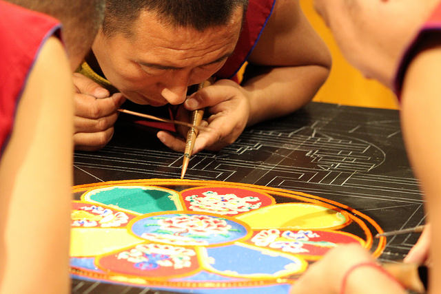 A Tibetan monk works on a sand mandala in the Doane Hall of Art on Tuesday Feb. 28, 2017. The monks were brought to campus by the Office of Spiritual and Religious Life as part of the Year of Mindfulness. Upon completion of the sand mandala, the monks destroy the project to symbolize disattachment, which is the belief that everything that exists now will at some point cease to exist.