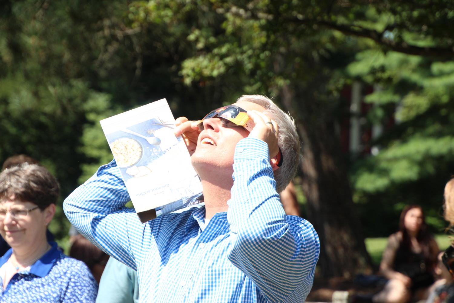 JOSEPH TINGLEY / THE CAMPUS Director of Career Education Jim Fitch uses special glasses to view the eclipse on Monday, Aug. 21, 2017 outside Newton Observatory.