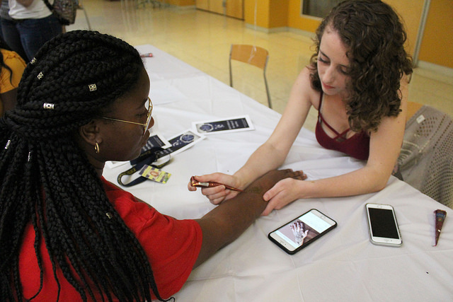 Olivia Heeb, '19, gives Benedicte Musimisa, '21, a henna tattoo at the Islamic Cultural Association's event to celebrate Eid Al-Adha on Sunday, Sept. 17, 2017.