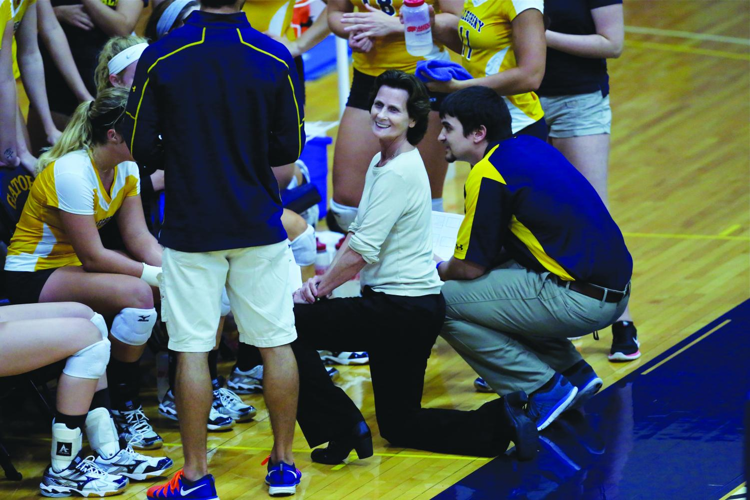 Coach Bridget Sheehan smiles in a huddle with her team during a volleyball game against Grove City College on Sept. 9, 2015.