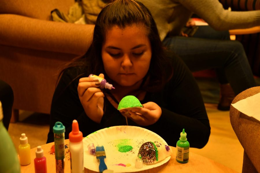 Corina Perez, '20, decorates sugar skulls in Grounds for Change on Wednesday, Nov. 1, 2017. The sugar skulls and altar will be on display in GFC until Nov. 8, 2017.