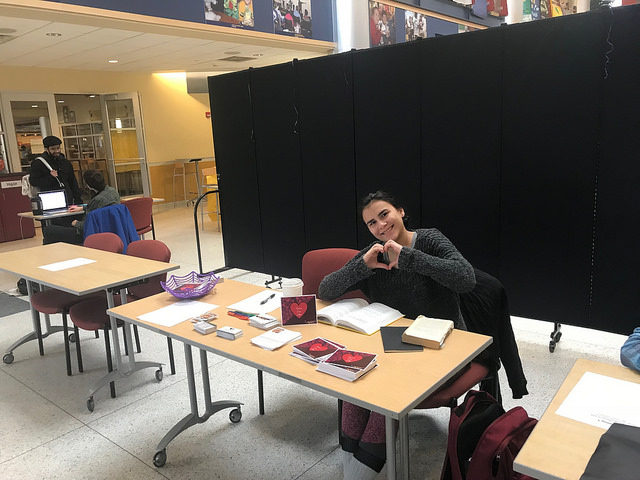 Valerie Calvo, '21, holds up a heart as she tables for the Why Not Us event in the Henderson Campus Center lobby Feb. 15, 2018.
