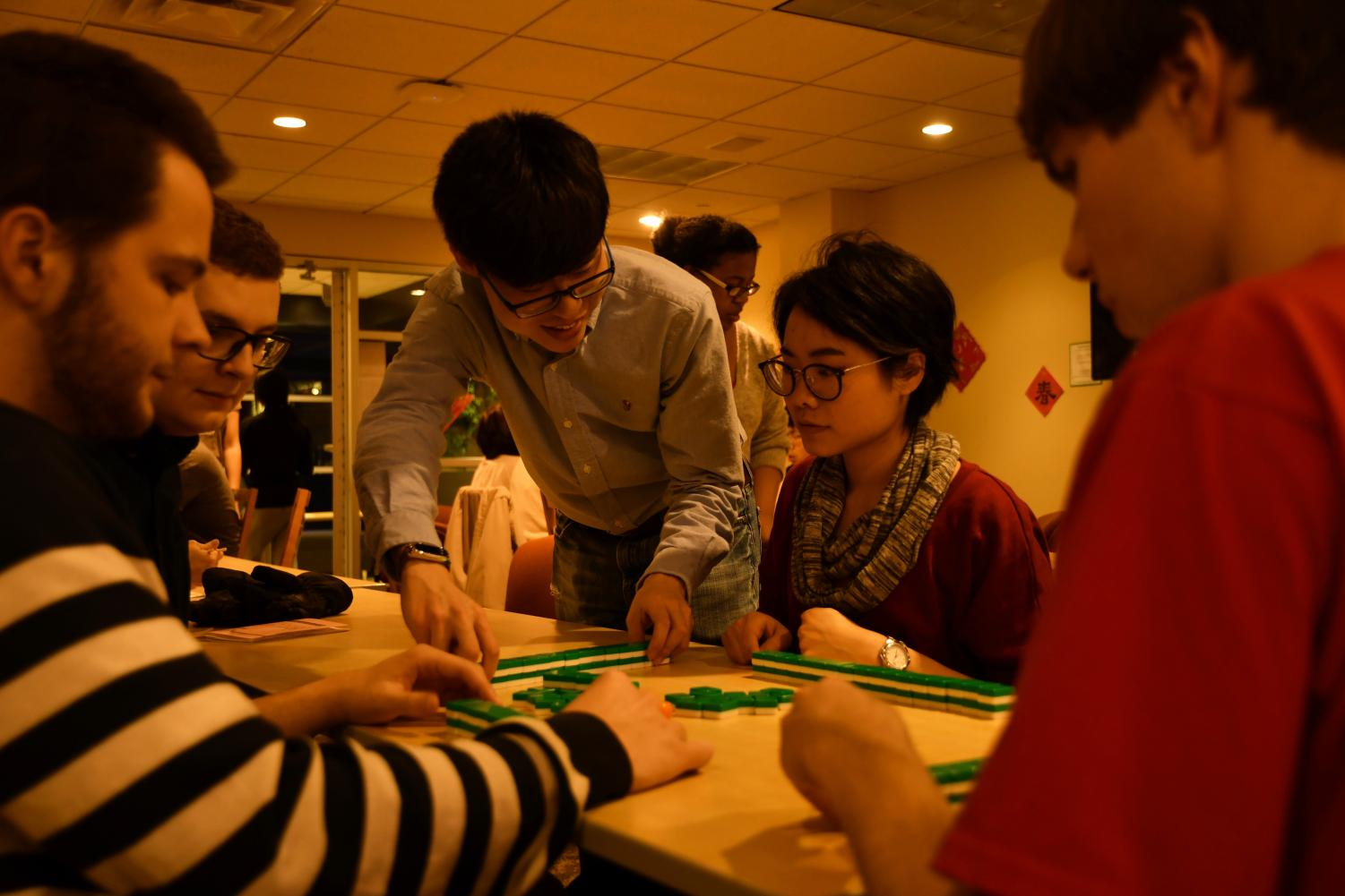 Xingbang Liu, '20, and Chih-Jung Chen, Chinese language teaching assistant, set up mahjong and teach Alec Tolmachoff, '20, Thomas Cassidy, '21, and Malcolm Willig, '21, how to play.