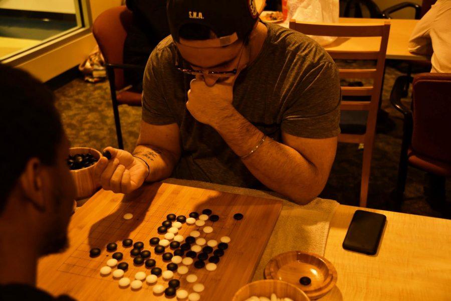Aaron Arden, '20, studies the board as he plays Go with Chris Miller, '19.