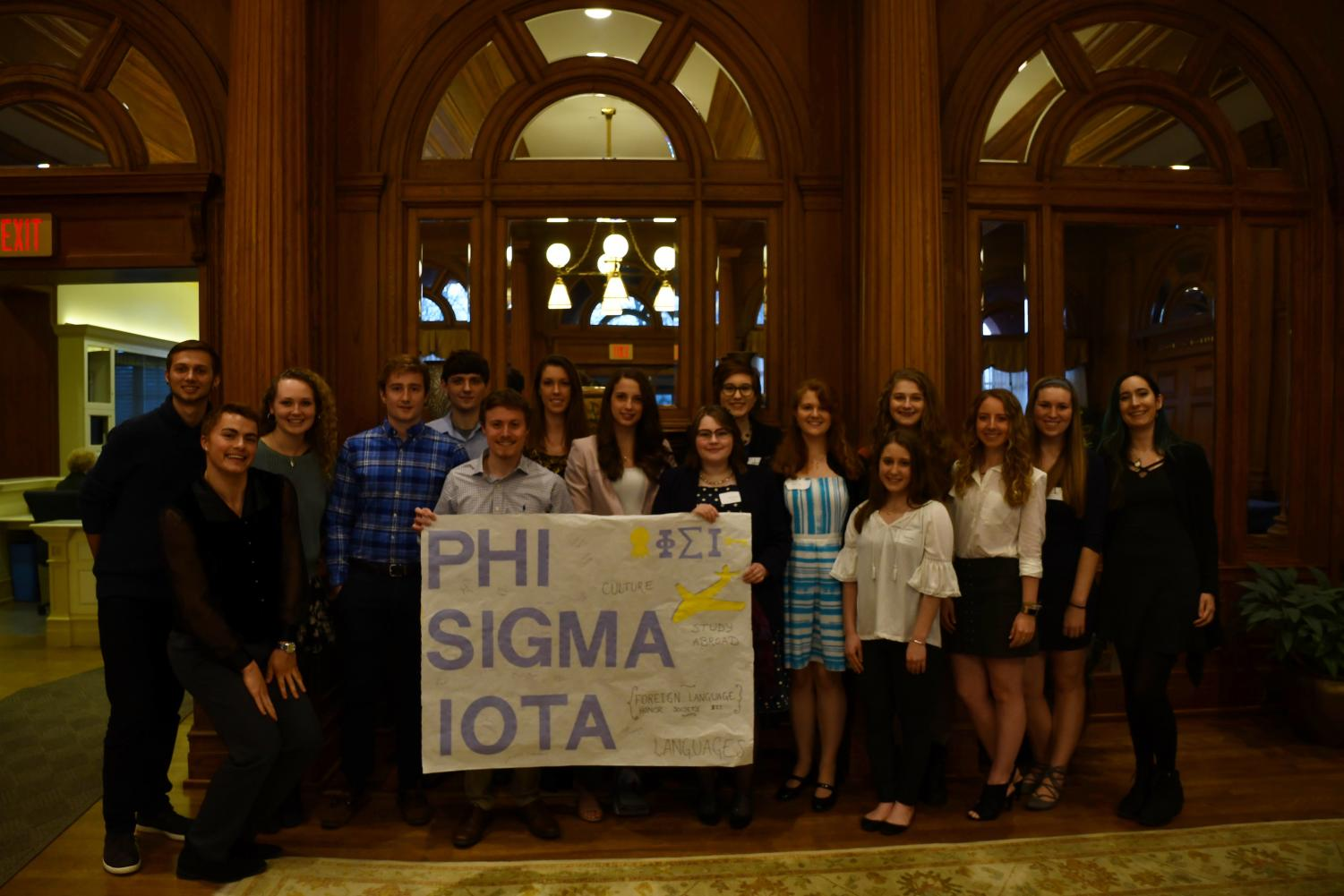 New members of the Phi Sigma Iota foreign language honor society pose with a banner after being inducted on Tuesday, April 10, 2018 in the Tippie Alumni Center.