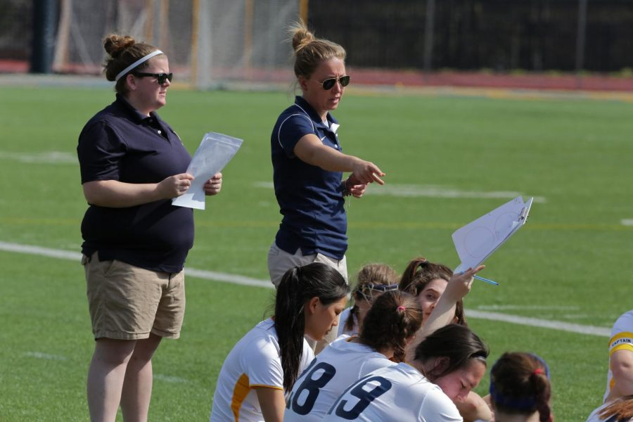 Head Lacrosse Coach Ashley Hughes, '08, talks to athletes on the sidelines during an April 22, 2015 game against Oberlin College.